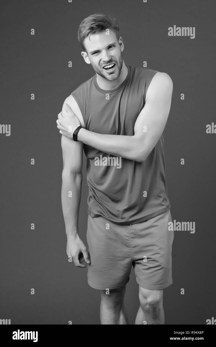 Feeling that pain again. Athlete injured shoulder joint. Man suffers old trauma chronic pain violet background. Sportsman risks taker exercising physical trauma. Guy painful face touches injured arm. - Stock Image