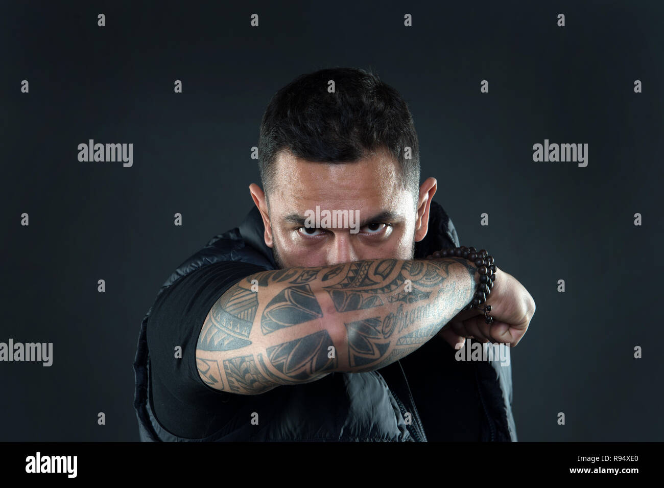 f52511ed3 Do tattoos hide lack of masculinity. Man brutal guy cover face with tattooed  arm.