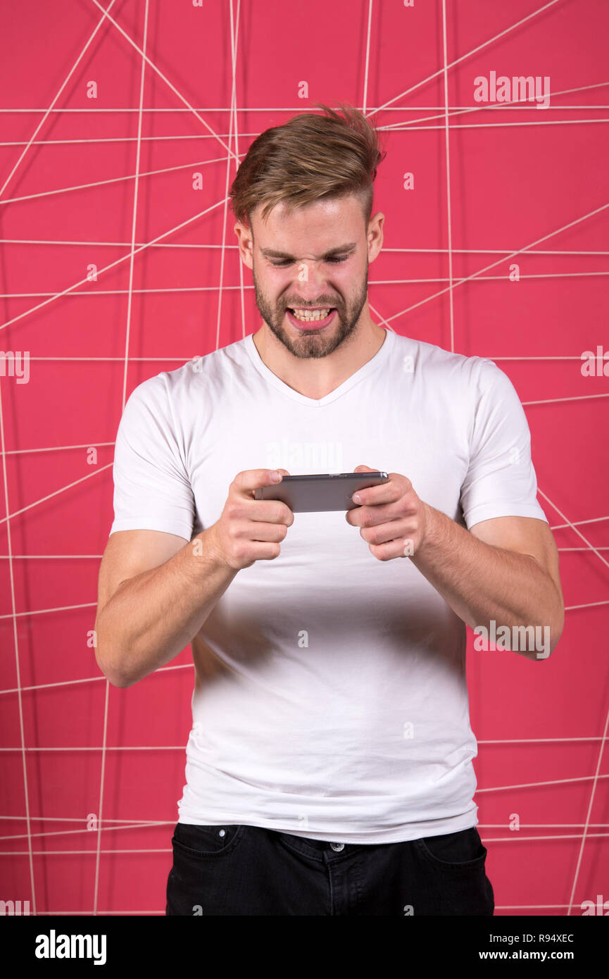 Excited about gaming. Guy play game smartphone gadget. Gamer aggressive face play online game smartphone. Application for smartphone concept. . Game addiction concept. Man not inseparable from phone. - Stock Image
