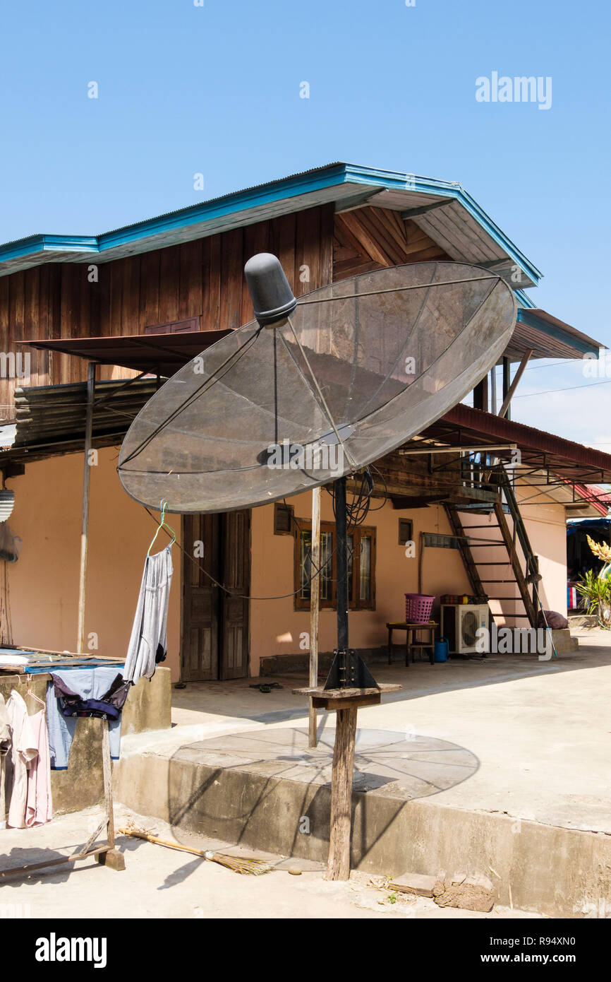 Large freestanding satellite dish outside a house at the Whisky village. Ban Xiang Hai, Luang Prabang, Louangphabang province, Laos, southeast Asia Stock Photo