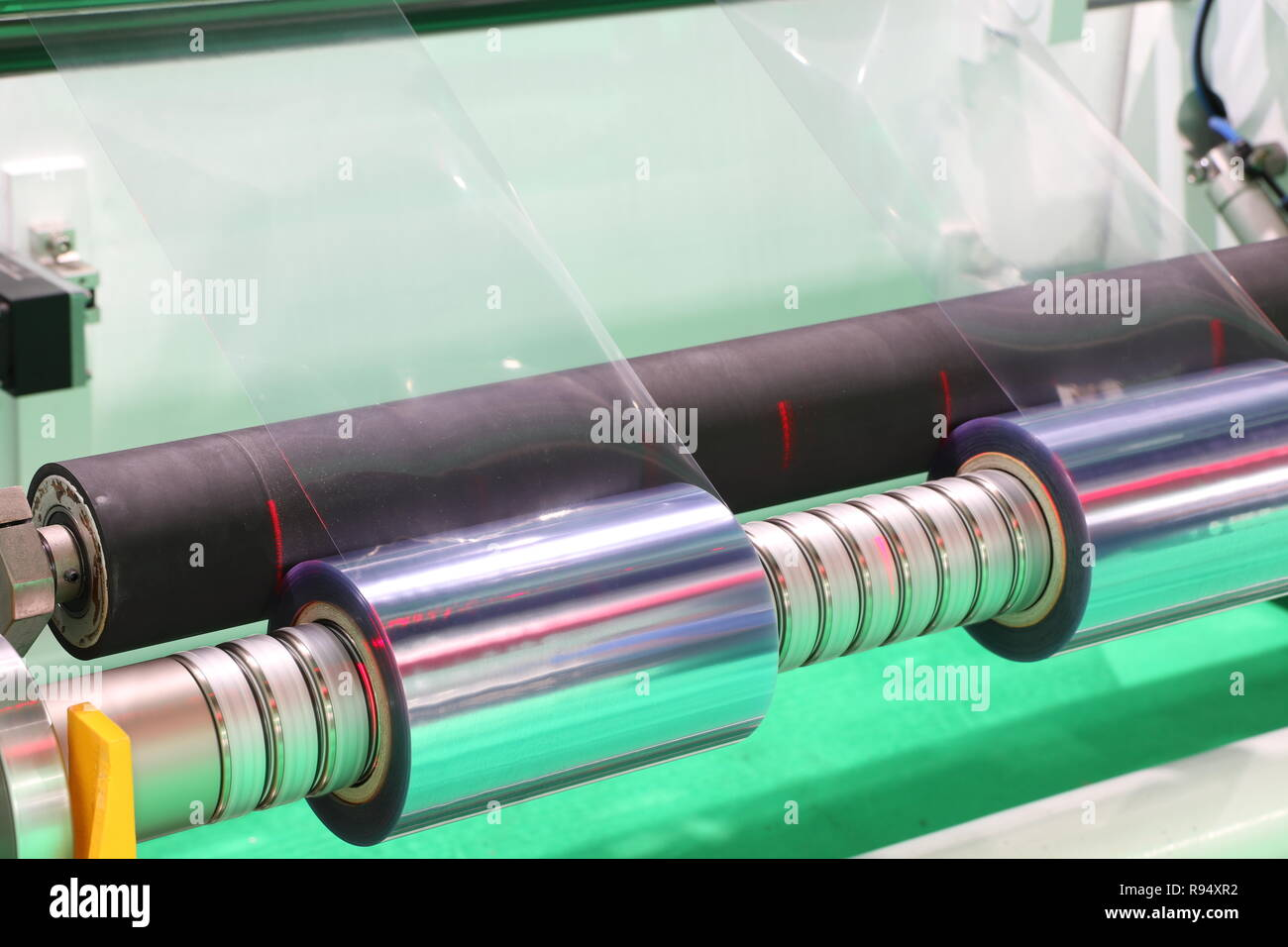Film Roll slitting machine ; a shearing operation that cuts a large roll of material into narrower rolls - Stock Image