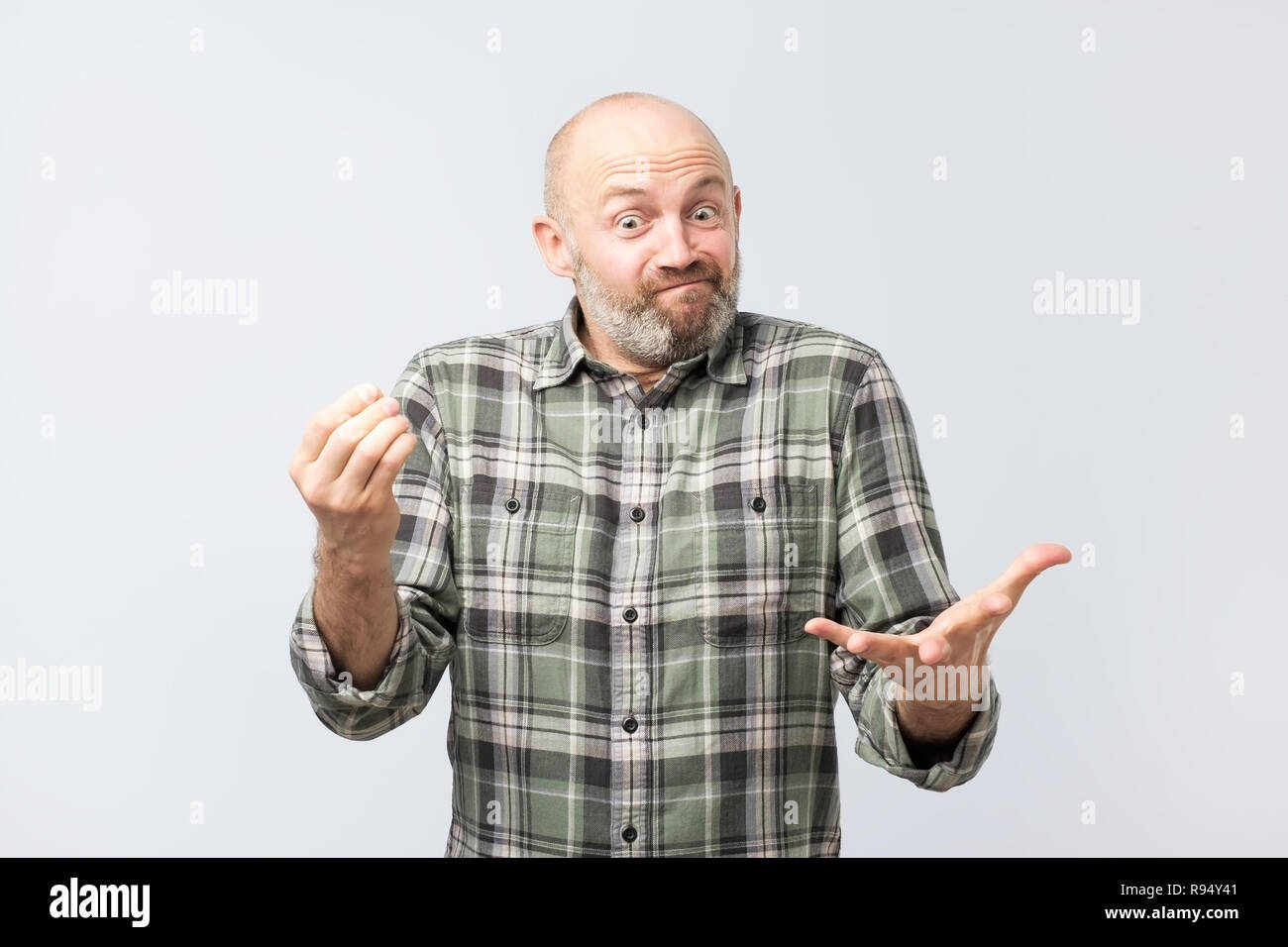 Mature european man explaining something simple being questioned someone, frowning and grimacing - Stock Image