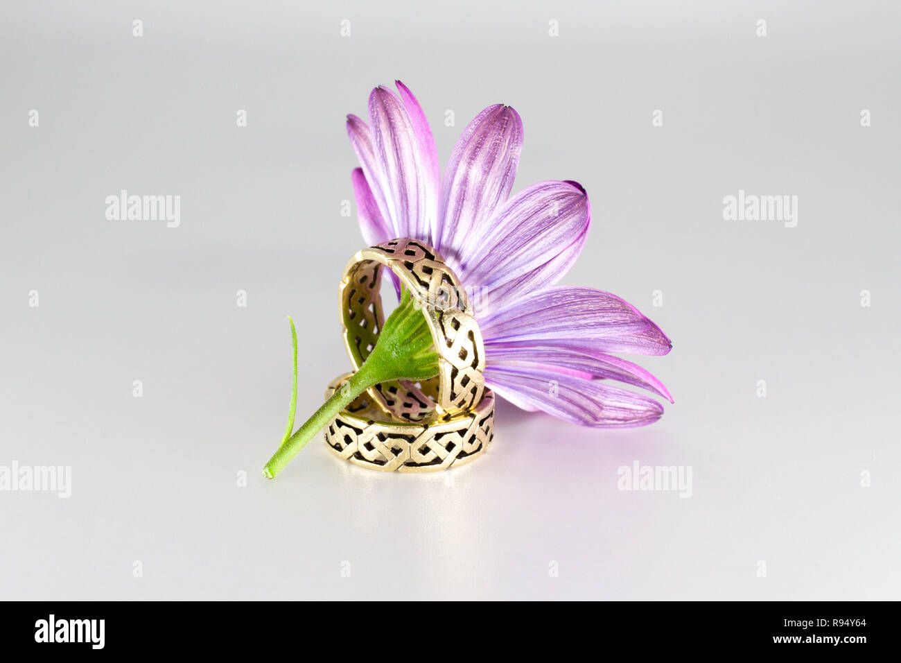 Golden wedding rings with Irish ornaments beside lilac flower - Stock Image
