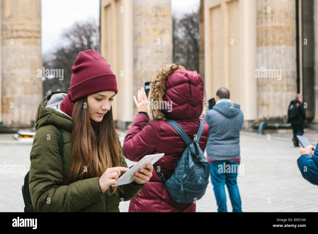A beautiful tourist girl uses a tablet in the square next to the Brandenburg Gate in Berlin. Nearby unrecognized people take photos of sights. People and modern technology. Tourism - Stock Image