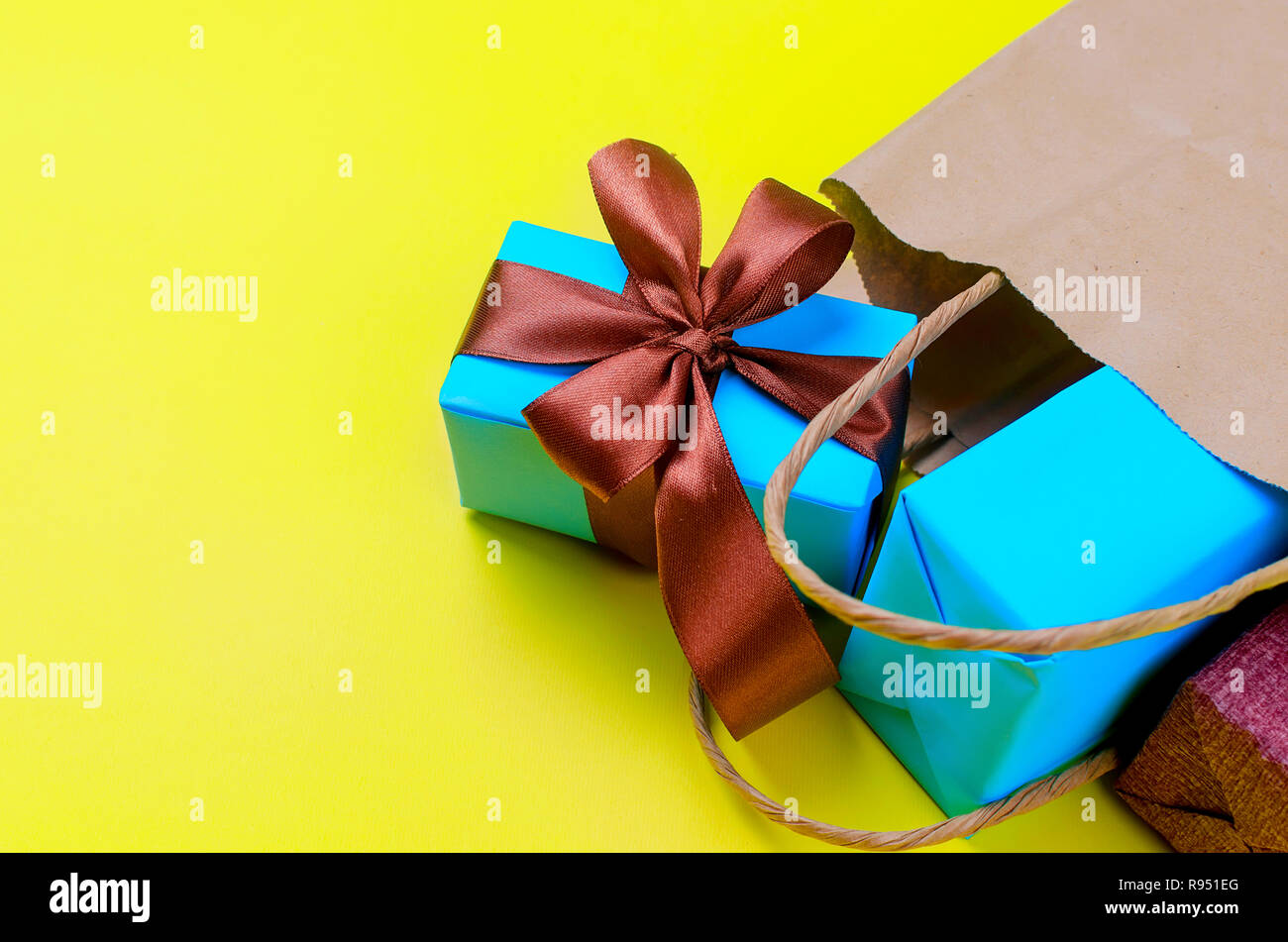 blue gift boxes decorated with a brown bow fall out of the crafting bag lie on a yellow background - Stock Image
