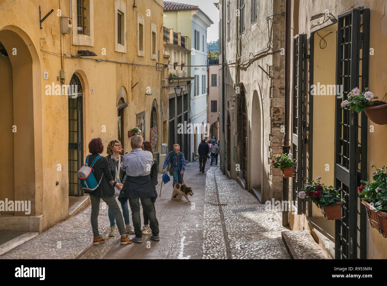 Tourists and local people at Via del Mercato, street in historic center of Spoleto, Umbria, Italy - Stock Image