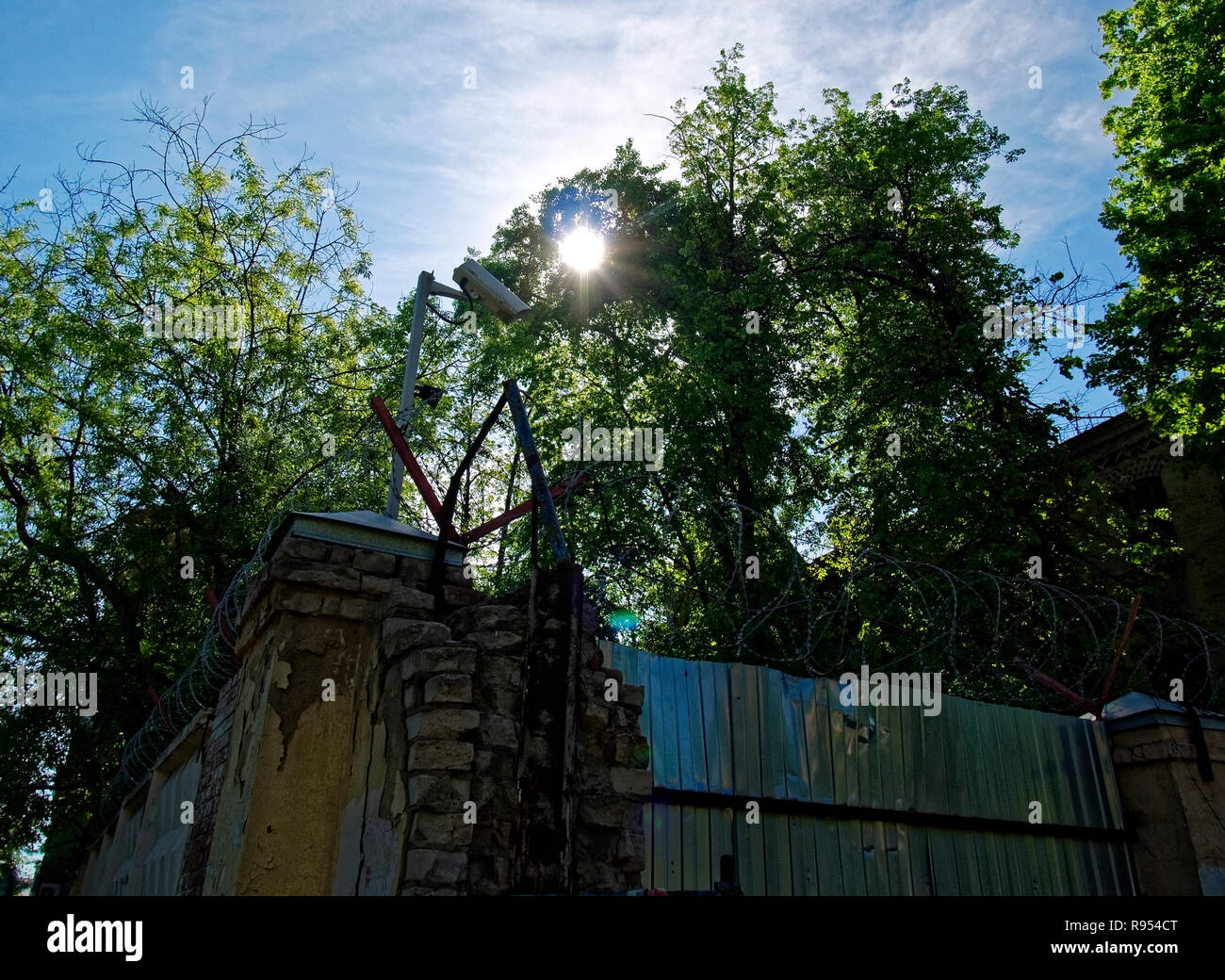 barbed wire over brick fence in spring, Moscow Stock Photo