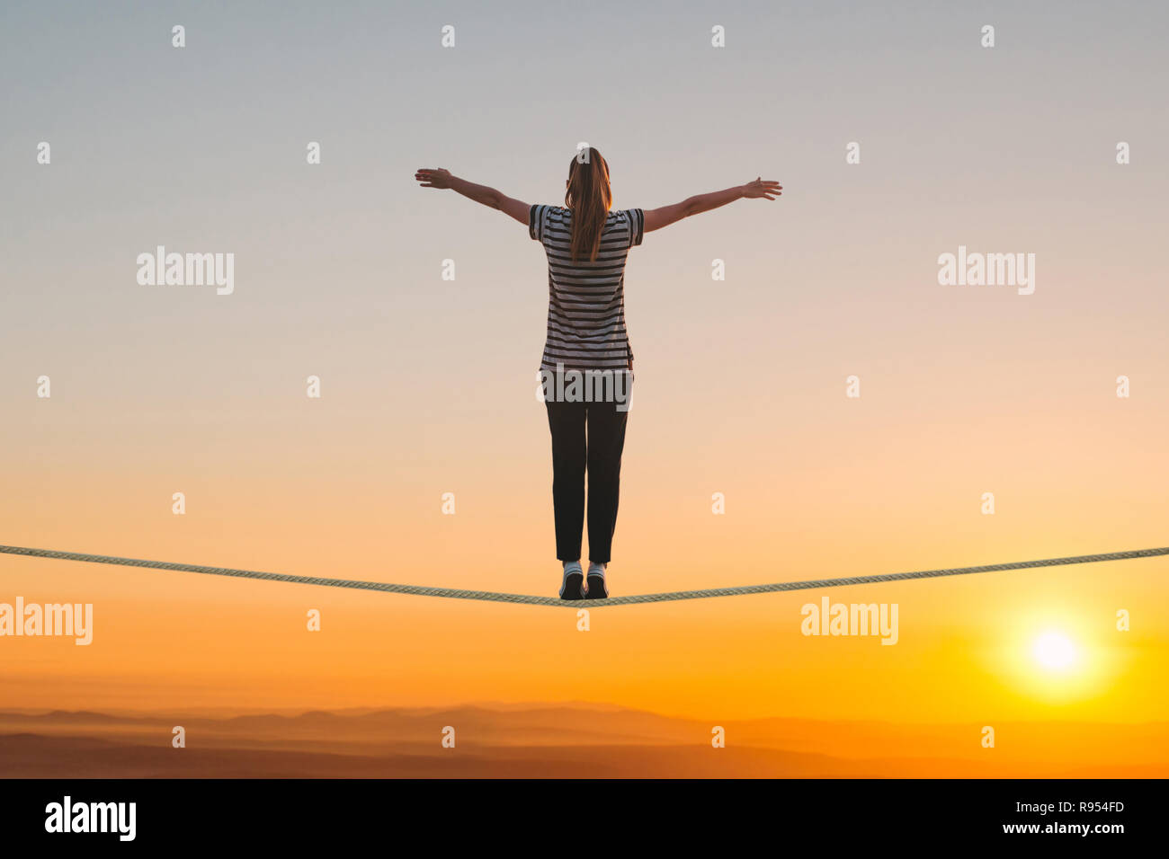 A girl stands on the rope and raises her hands against the sunset. The concept of freedom and confidence. - Stock Image
