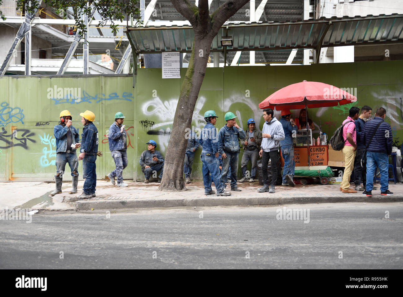 South American construction workers taking a coffee break at a building construction work site in downtown Bogota. - Stock Image