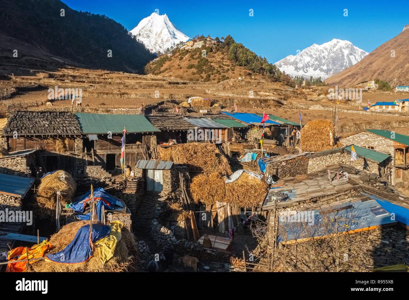 The ethnically Tibetan village of Lho in the Manaslu region of the Nepal Himalayas lies on the Manaslu Circuit trekking route. Manaslu peak beyond - Stock Image