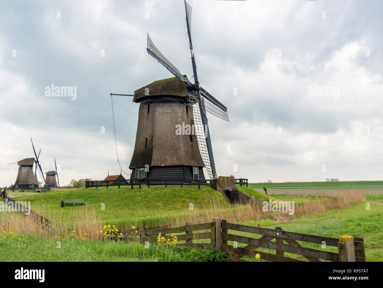 The Schermerhorn Museum Mill in a row of three windmills on a blustery cloudy day at Schermerhorn, North Holland, The Netherlands - Stock Image