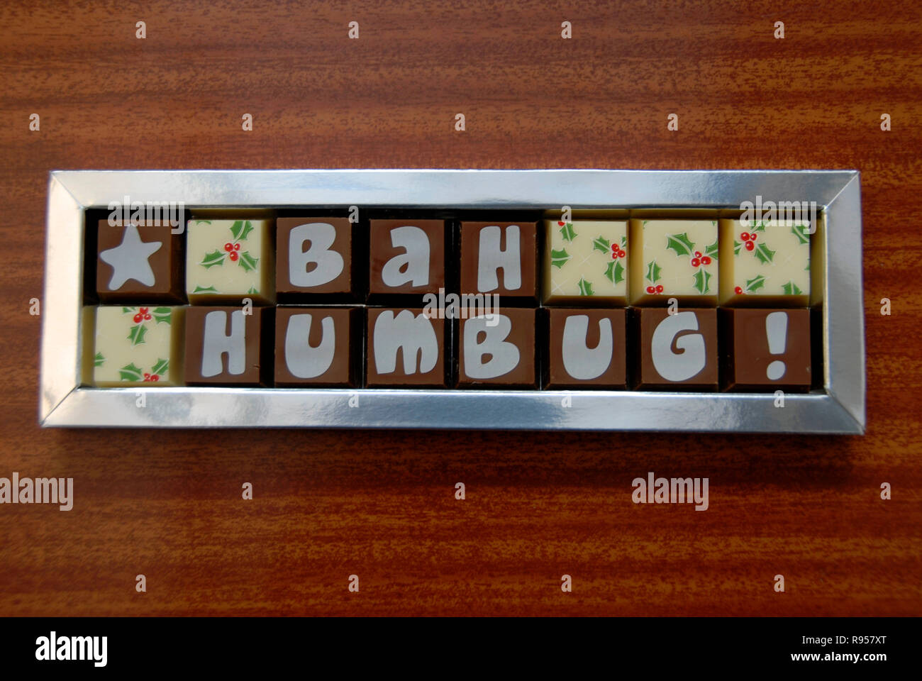 Box of Christmas sweets with the words 'Bah Humbug!' showing on the wrappers - Stock Image