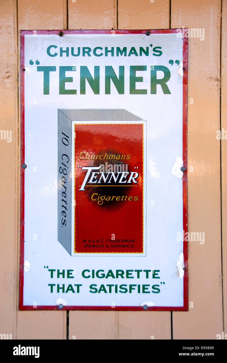 Old metal advertising panel for Churchman's Tenner cigarettes on display on wall at railway station - Stock Image