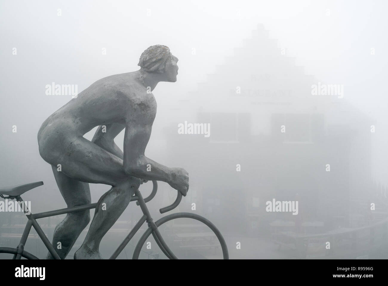 Restaurant / bar and statue for Tour de France cyclist Octave Lapize at the Col du Tourmalet in thick mist in the Pyrenees, France Stock Photo
