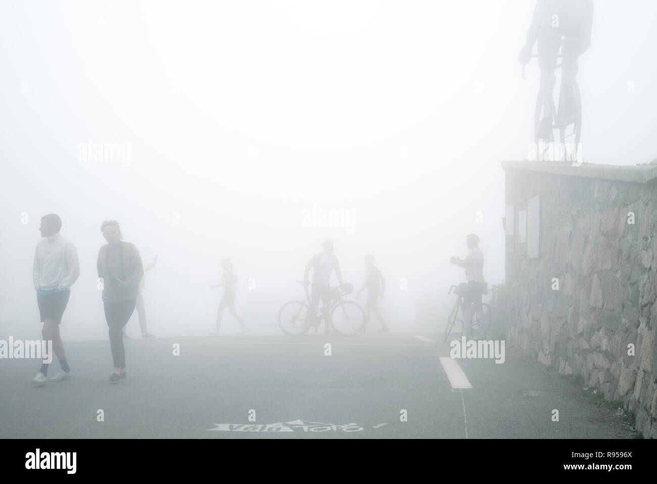 Tourists watching the statue for Tour de France cyclist Octave Lapize at the Col du Tourmalet in thick mist in the Pyrenees, France Stock Photo