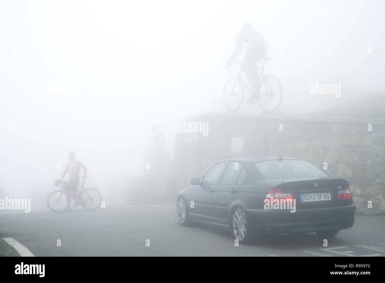 Cyclist crossing road in front of the statue for Tour de France winner Octave Lapize at the Col du Tourmalet in thick mist in the Pyrenees, France Stock Photo