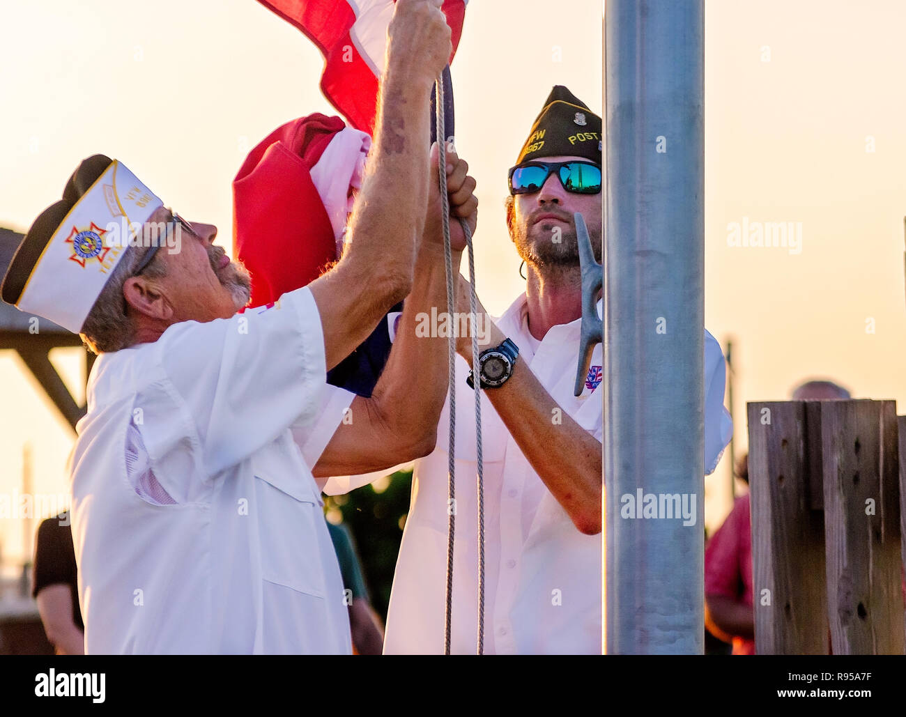 VFW Post members lower the American and Texas flags at sunset during a Hurricane Harvey memorial service in Port Aransas, Texas. - Stock Image