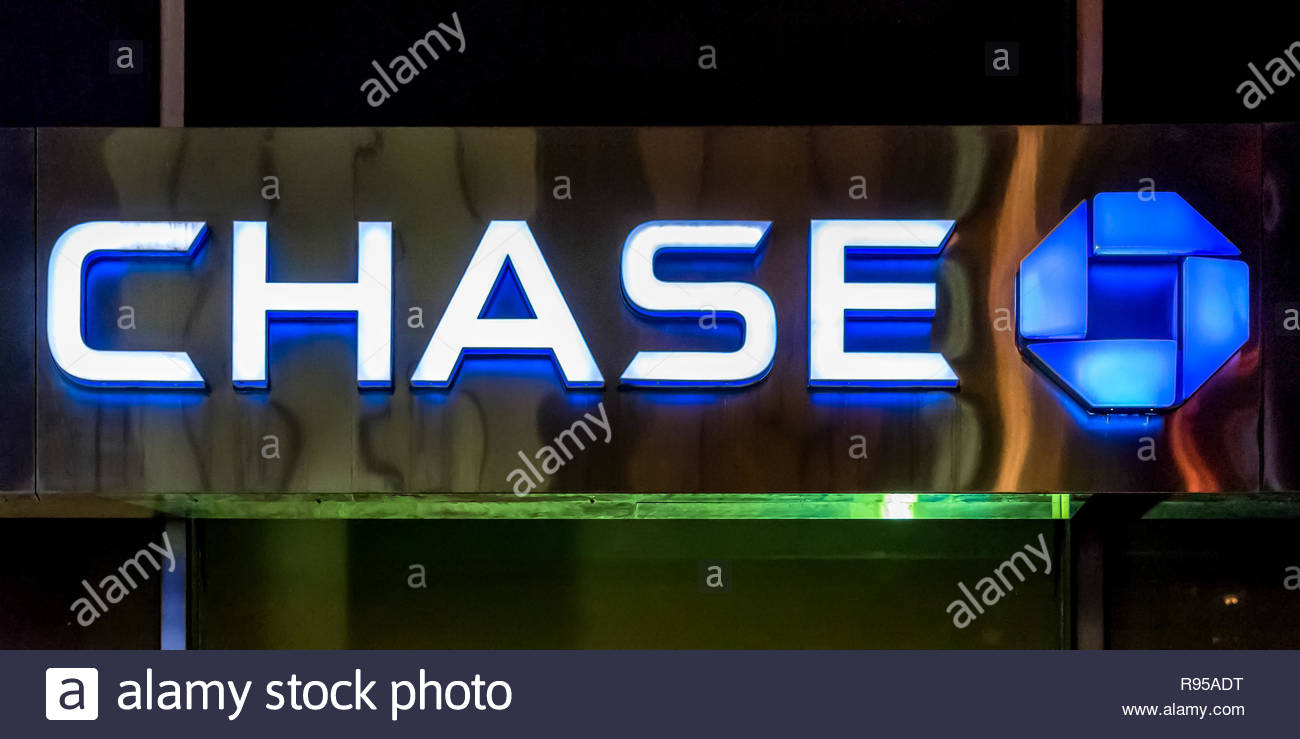 Financial institutions in New York: Chase bank signage and logo glowing on its building in NYC.  JPMorgan Chase Bank, N.A., doing business as Chase, i - Stock Image
