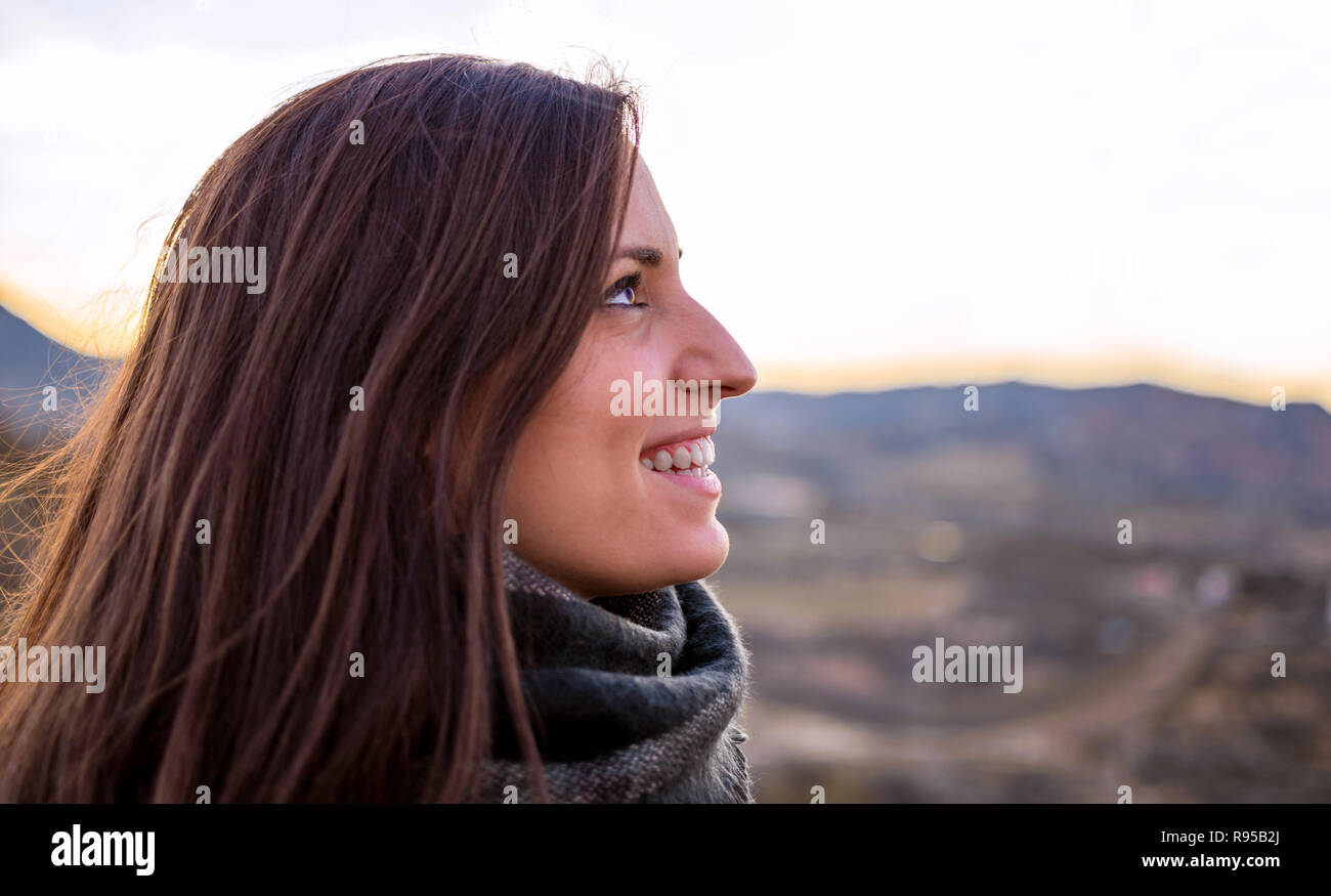 Smiling woman portrait side view. Young caucasian Spanish girl against agriculture fields. Freedom in nature. Stock Photo