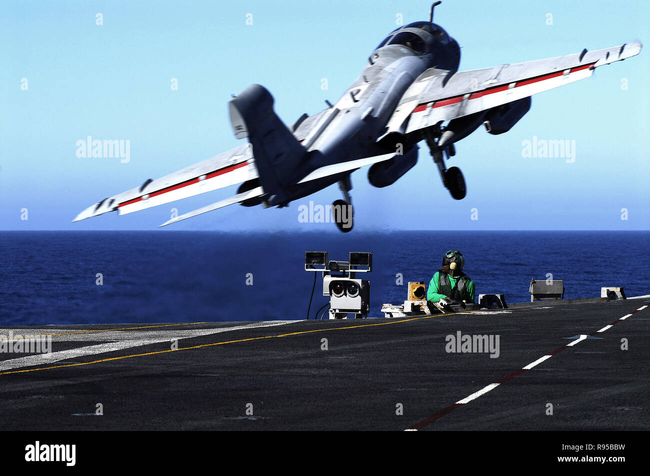 """An EA-6B Prowler assigned to the """"Yellowjackets"""" of Tactical Electronic Warfare Squadron One Three Eight (VAQ-138) takes off from the flight deck as an Aviation Boatswains Mate  prepares to launch the next aircraft aboard the Nimitz- class aircraft carrier USS John C. Stennis (CVN 74). U.S. Navy photo by Mass Communication Specialist 3rd Class Jon Hyde Stock Photo"""