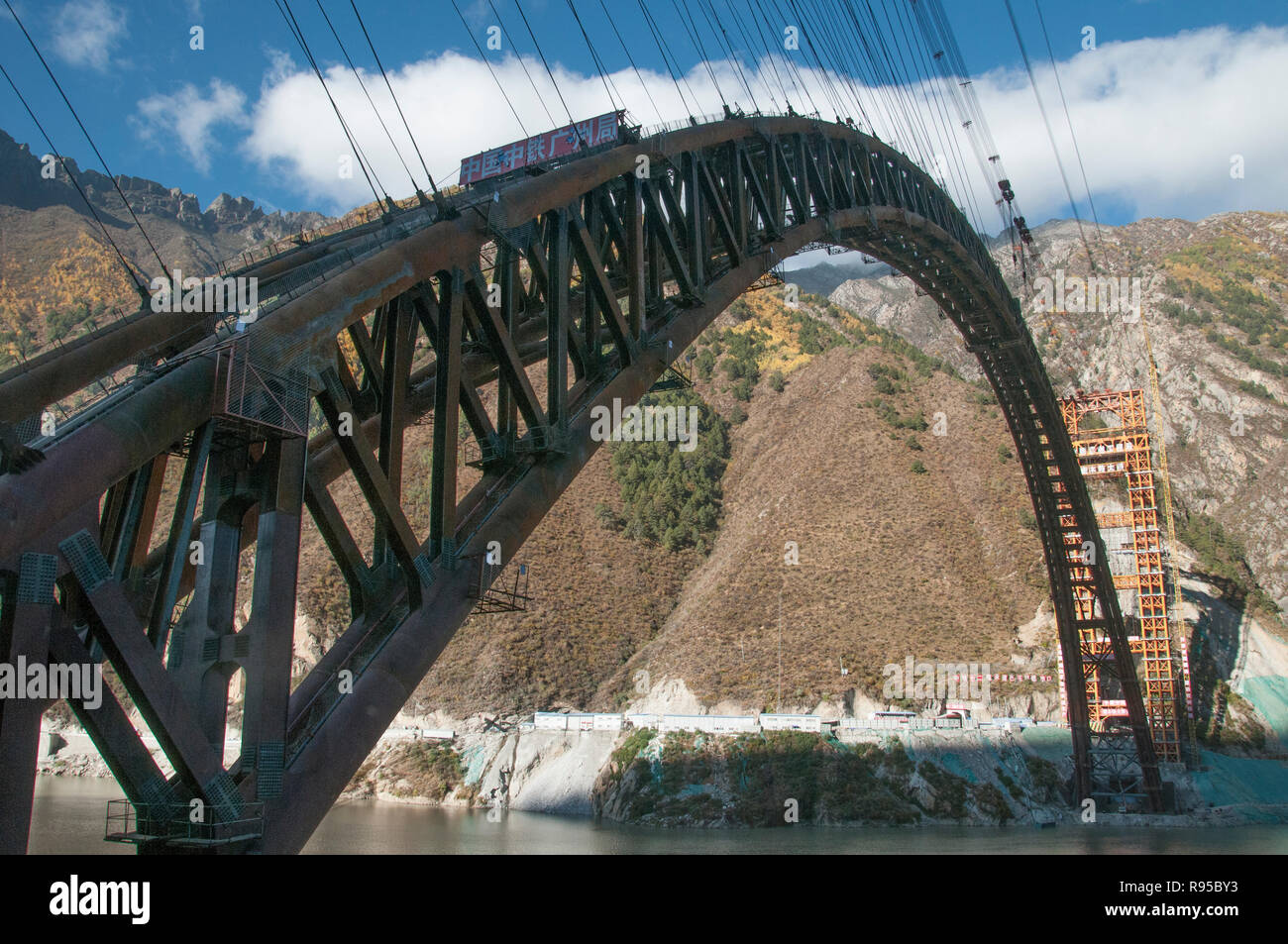Steel arch of a railway bridge under construction spans the Yarlung Tsangpo or Brahmaputra River in Tibet, China - Stock Image