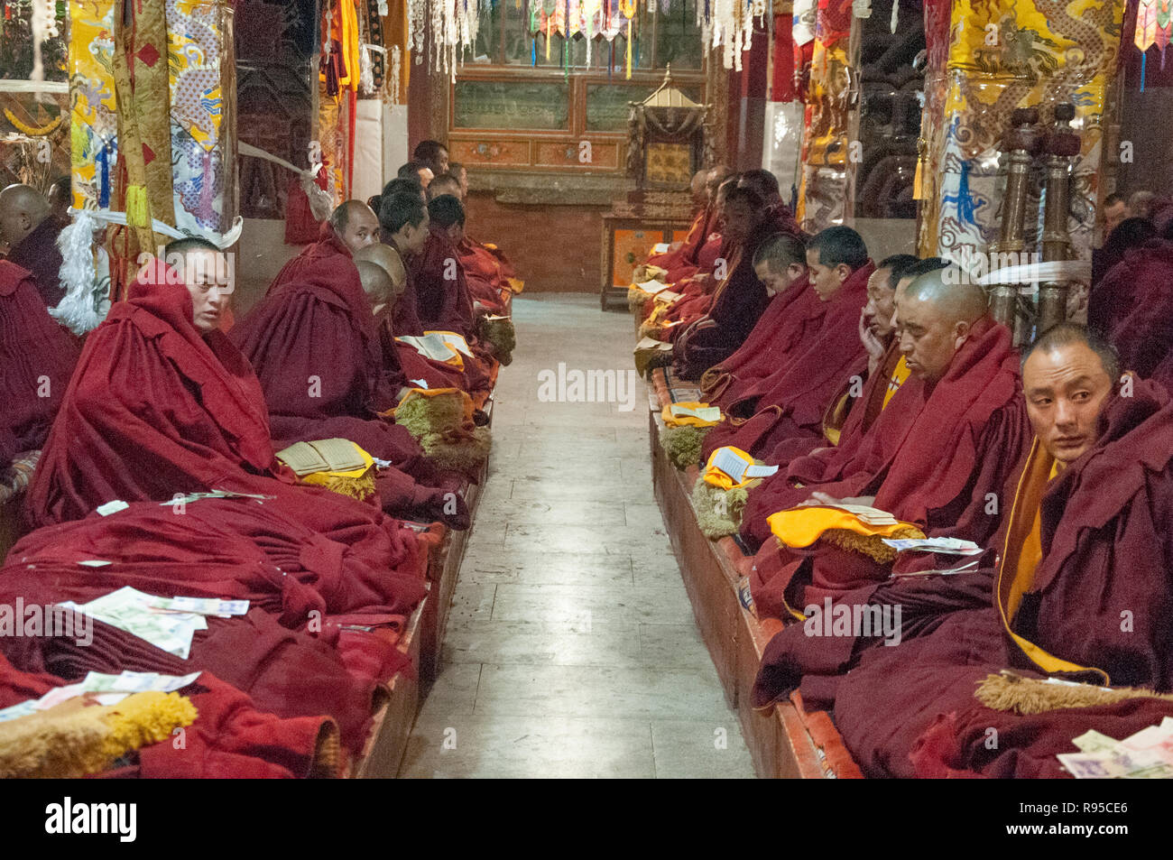 Buddhist monks recite their scriptures in the main hall of Ganden Monastery, outside Lhasa, Tibet, China - Stock Image