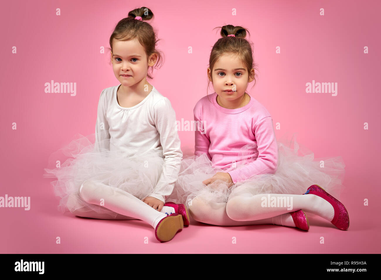 two cute little girls in white tulle skirts on a pink background - Stock Image