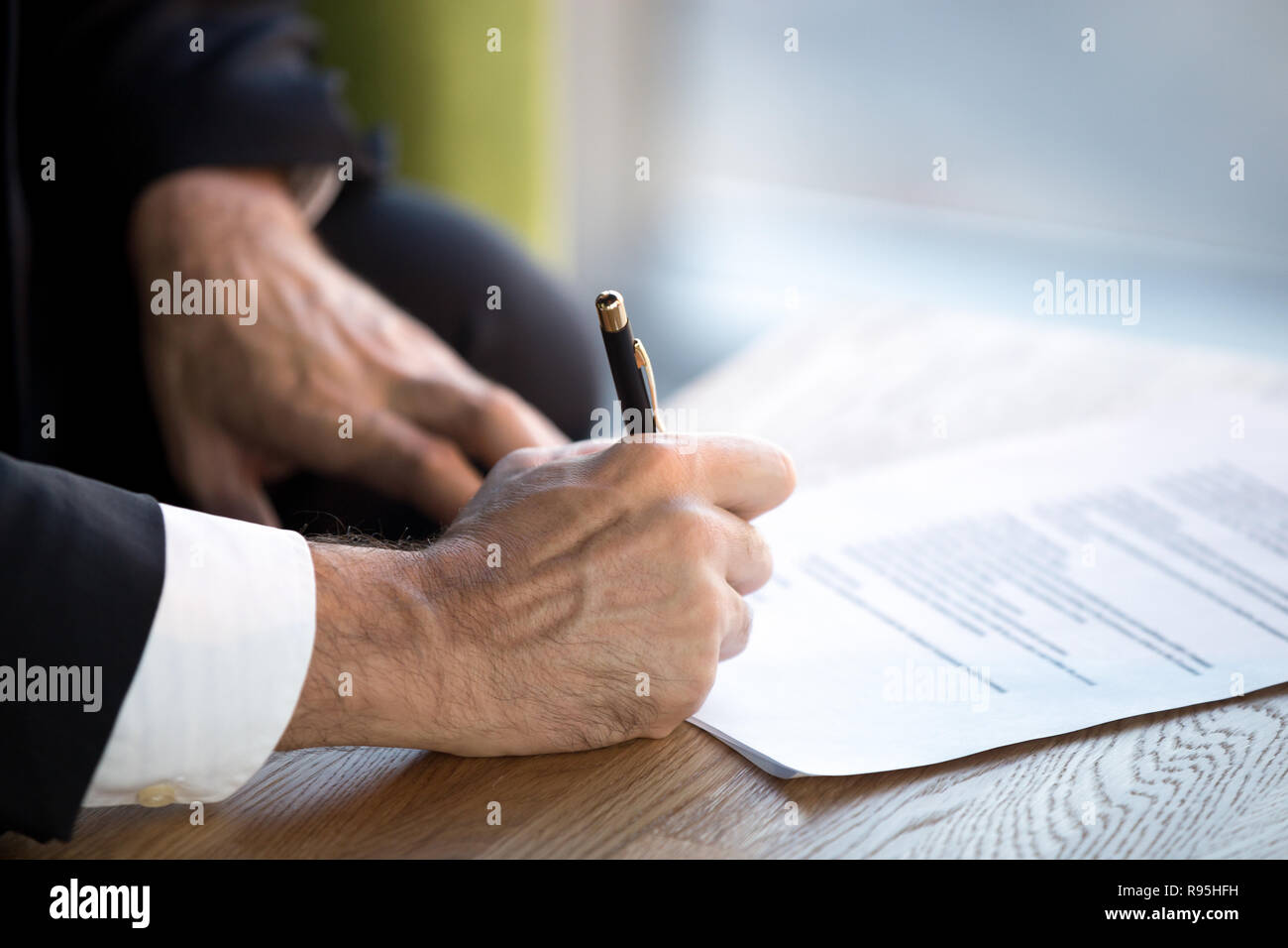 Close up male hands puts his signature on official document - Stock Image