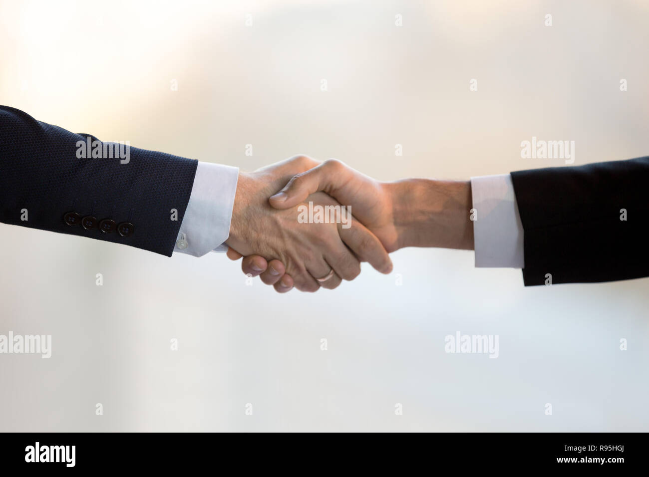 Close up two businessmen in suits shaking hands - Stock Image