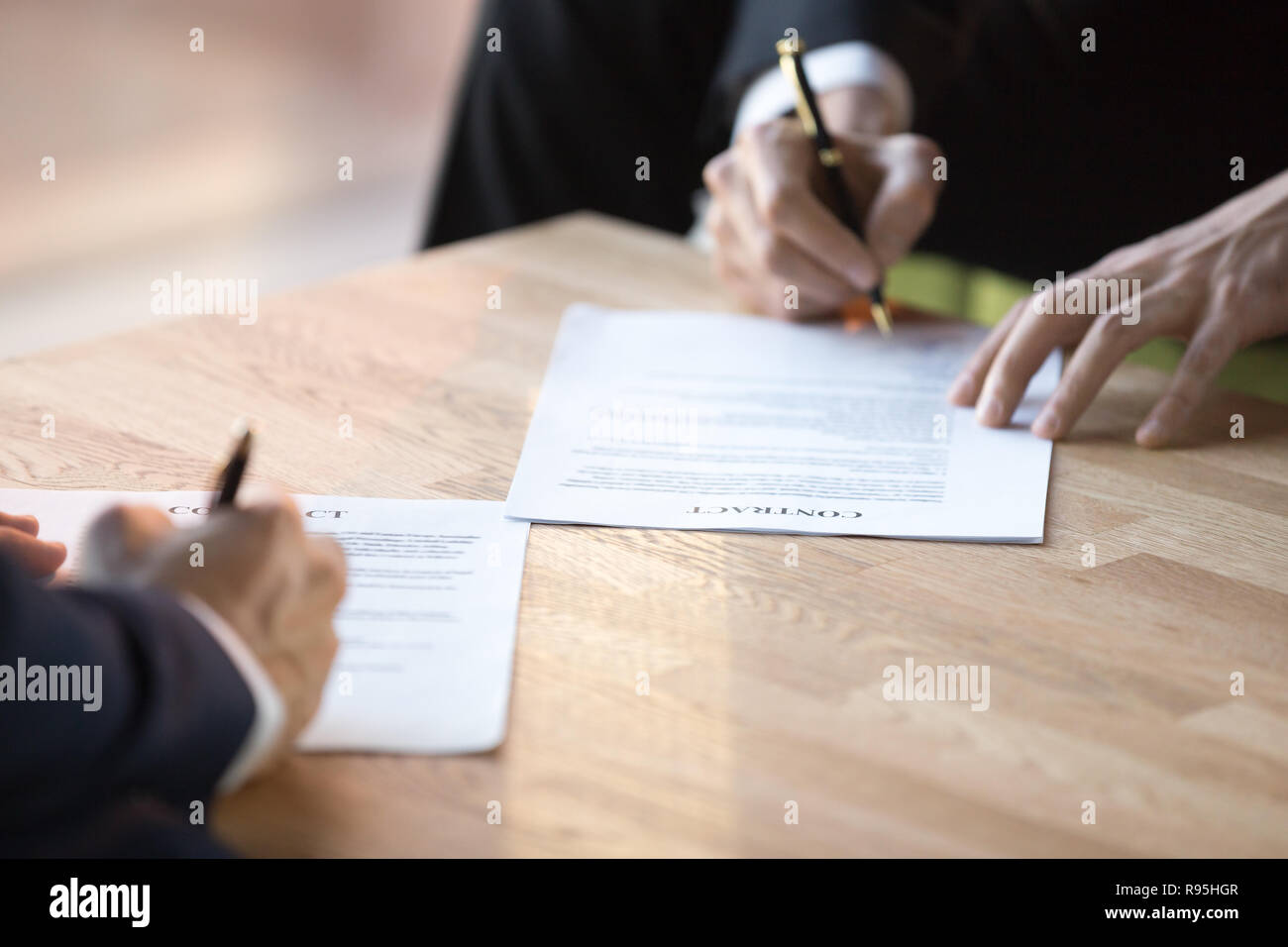 Close up businessmen hands holds pens signing contract  - Stock Image