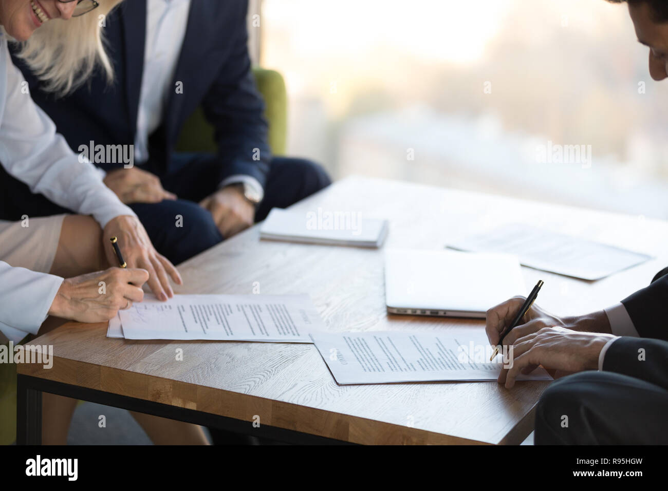 Mature businesswoman and businessman signing contract after nego - Stock Image