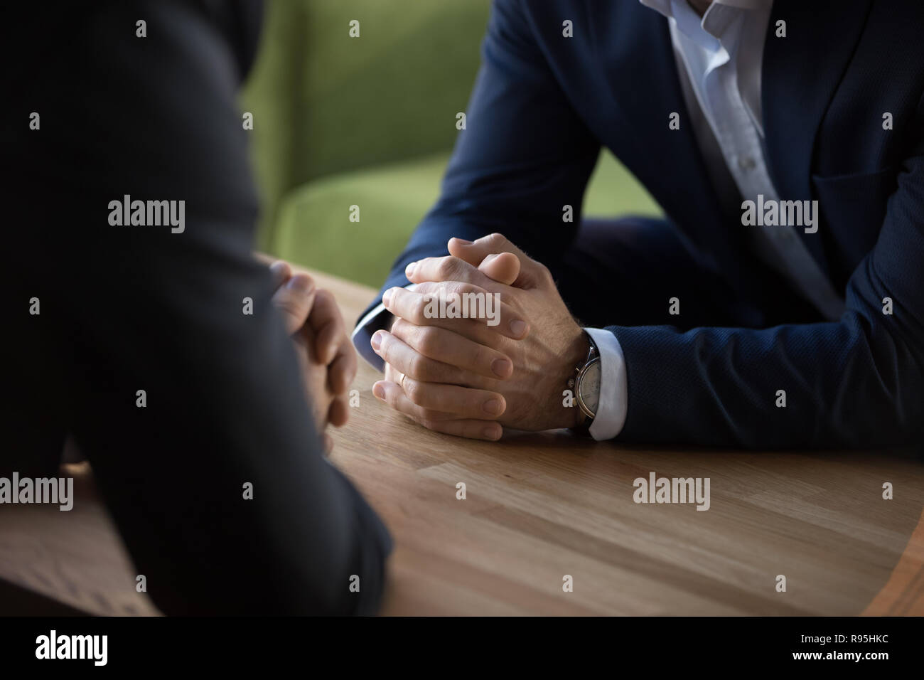 Confident businessmen sitting opposite of each other at business - Stock Image