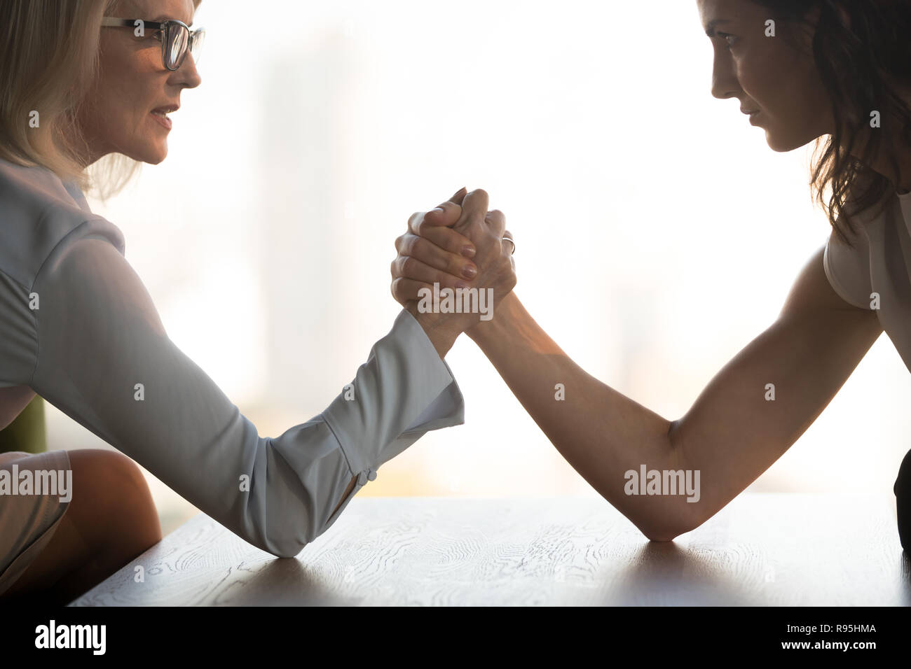 Young brunette and aged blond businesswomen arm wrestling - Stock Image