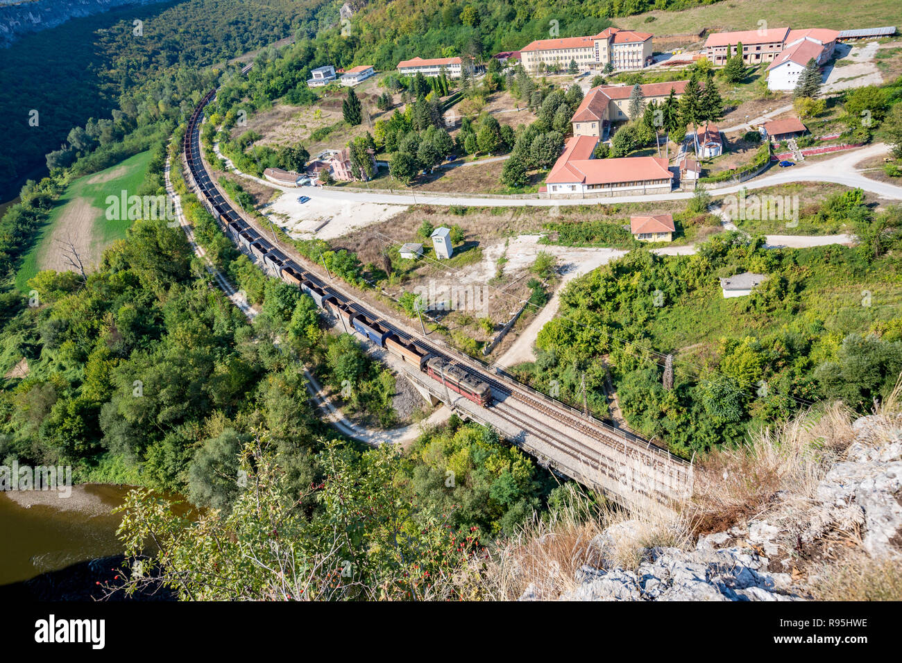 Long empty freight train with many goods wagons passes near the psychiatric hospital near Karlukovo, Northern Bulgaria in sunny autumn day, landscape  - Stock Image