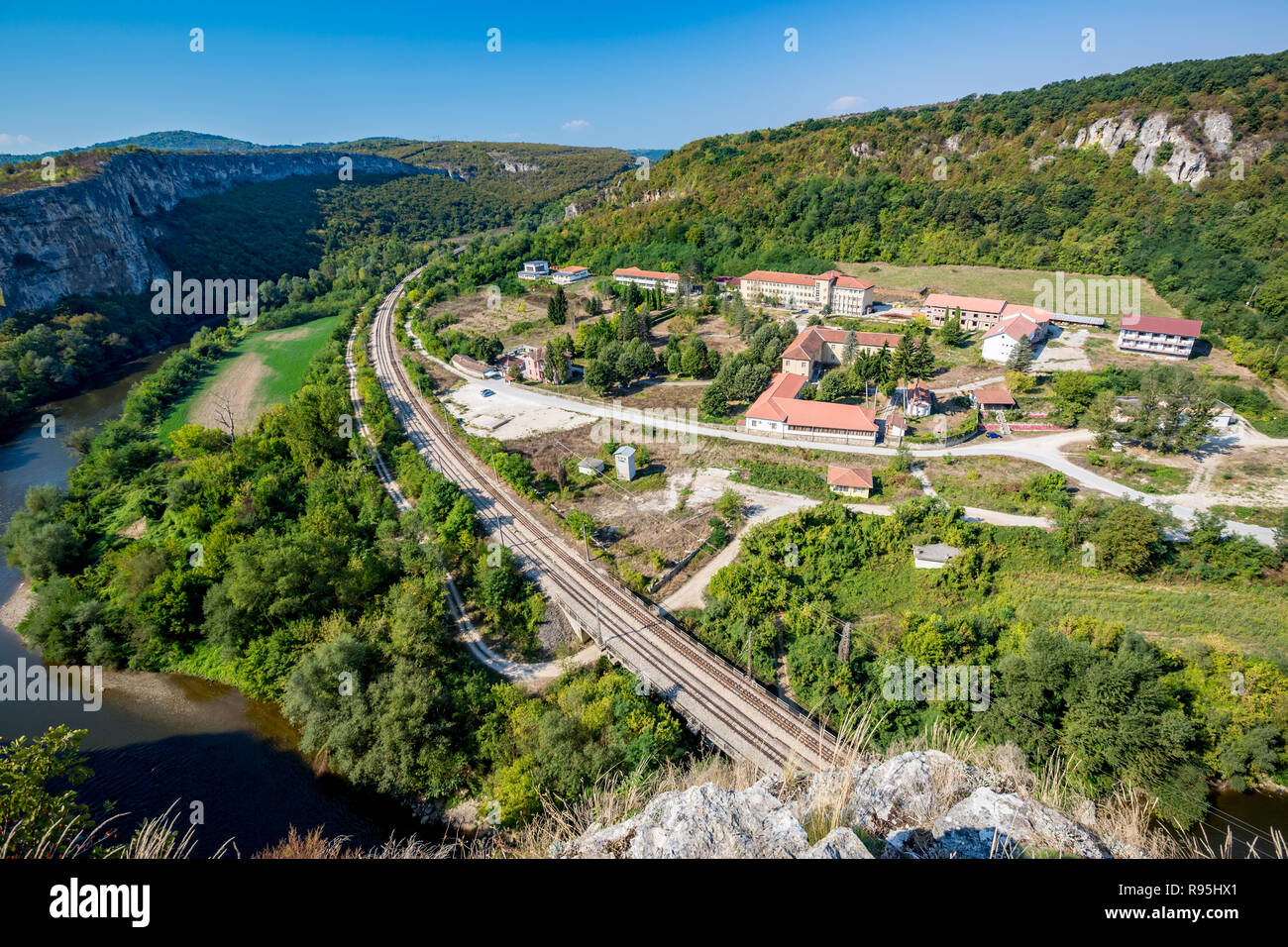 Long empty railway near the psychiatric hospital near Karlukovo, Northern Bulgaria in sunny autumn day, landscape from high above with Iskar river on  - Stock Image