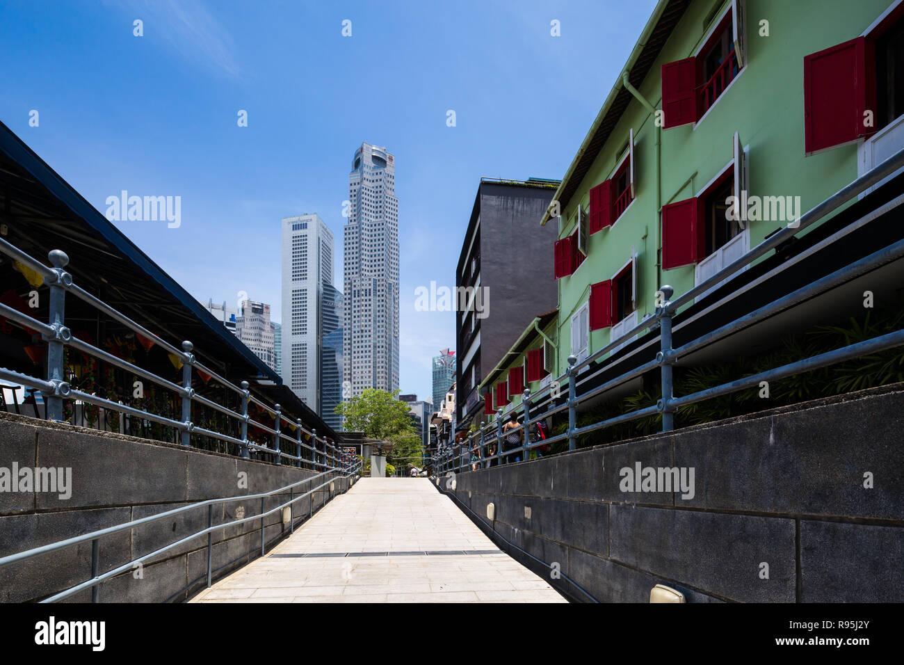 Long stretch of upslope path to viewing of One Raffles Place skyscraper from Boat Quay, Singapore. - Stock Image