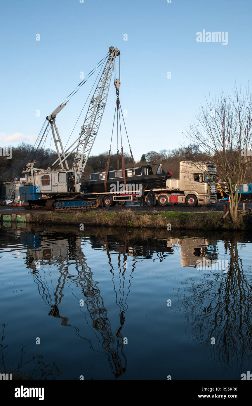 Lifting a narrow boat from a HGV trailer into the canal. - Stock Image