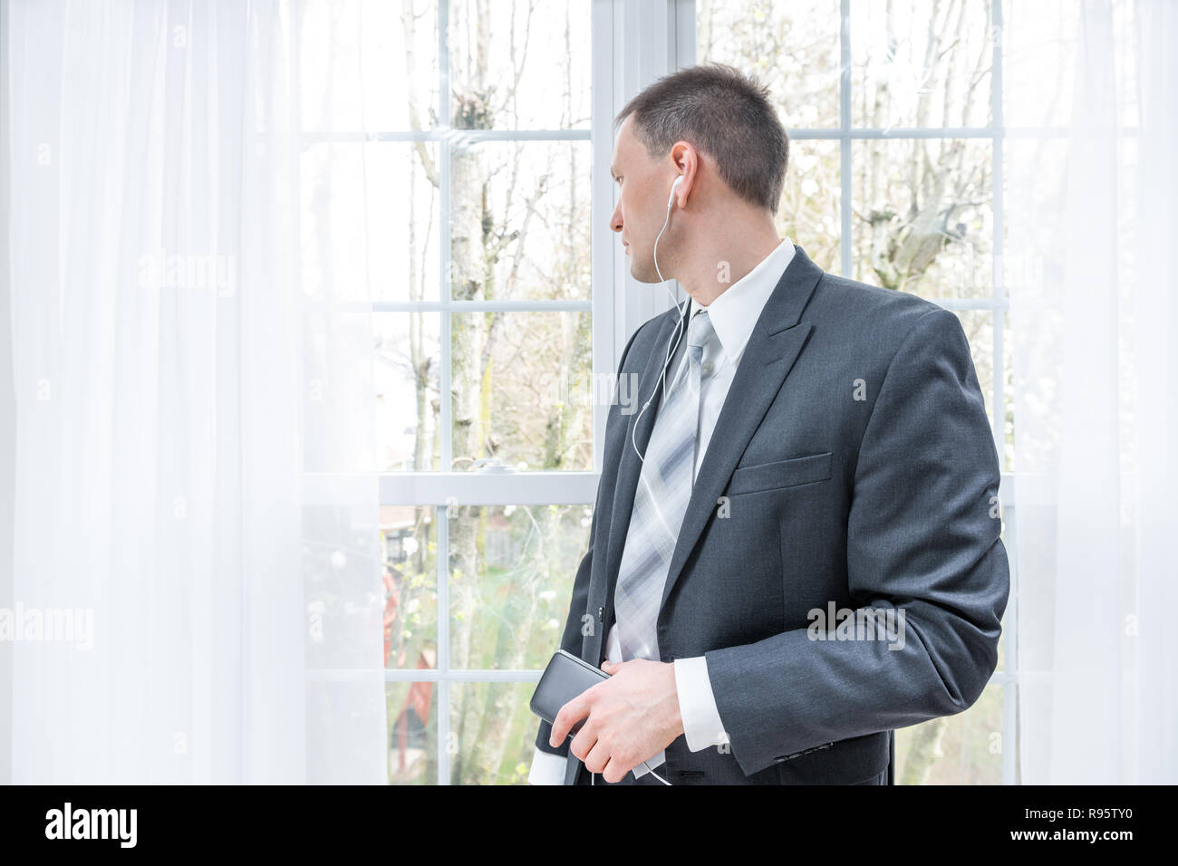 Closeup of young, happy smiling man, businessman, business suit, tie, standing by window in home, house room, white curtains, with earbuds headphones, - Stock Image