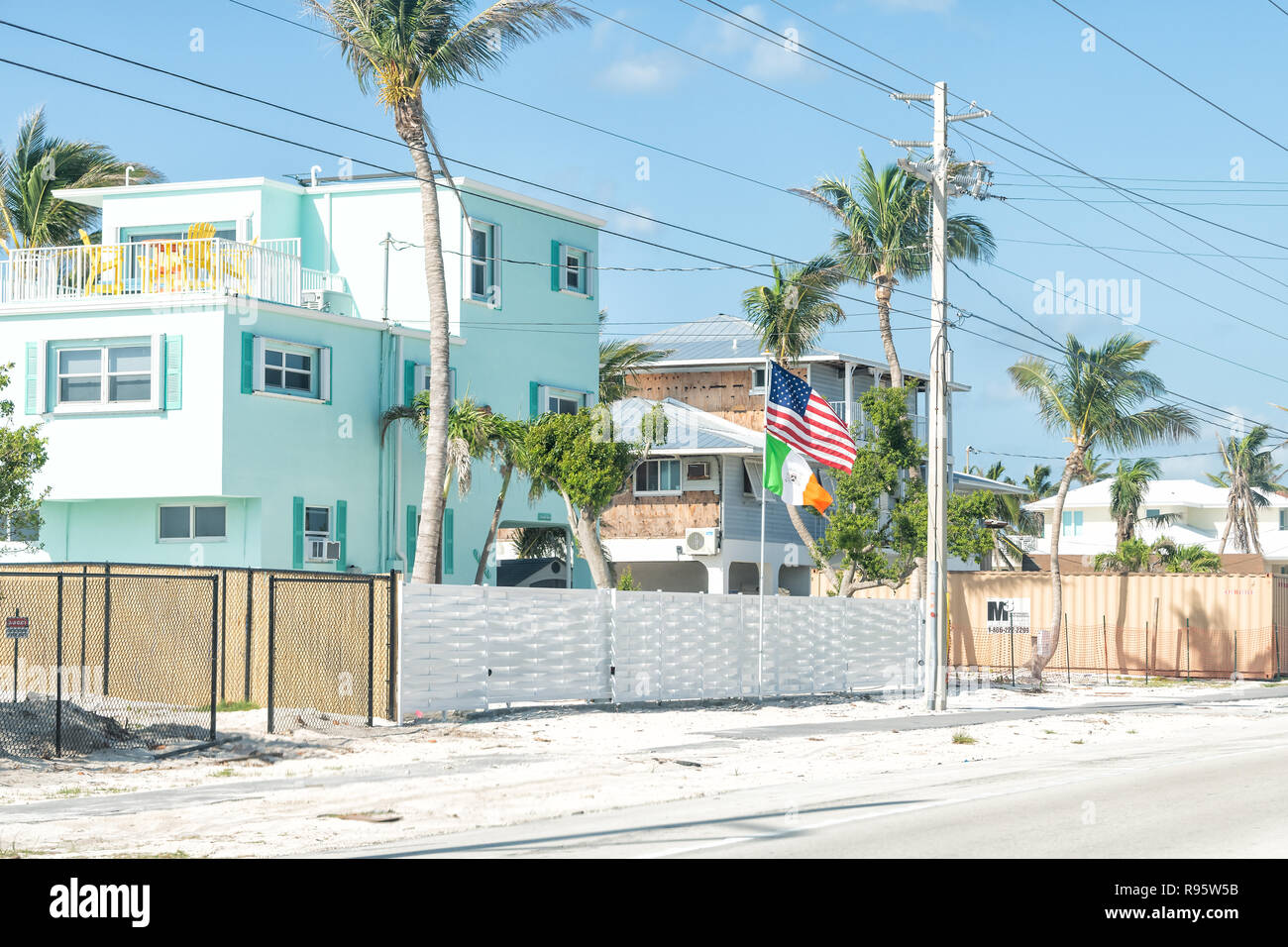 Long Key, USA - May 1, 2018: Turquoise, teal, blue beach vacation houses, homes with palm trees in Florida at overseas highway road, street, American  - Stock Image