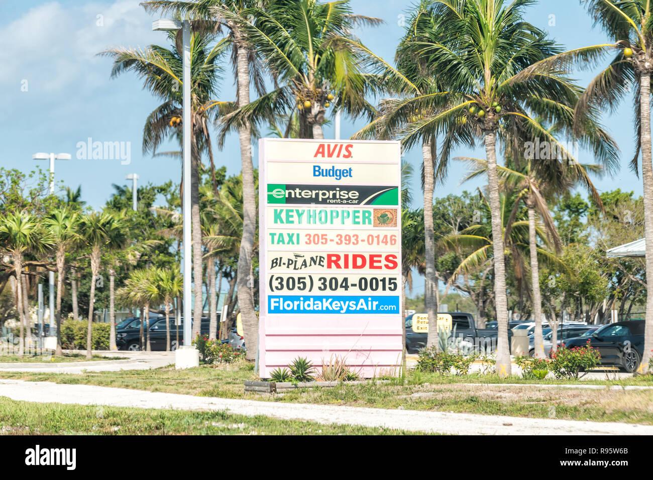 Marathon, USA - May 1, 2018: Road sign, billboard for Avis, Budget, Enterprise, keyhopper car rental, taxi, bi-plane rides, tourist activities in Flor - Stock Image