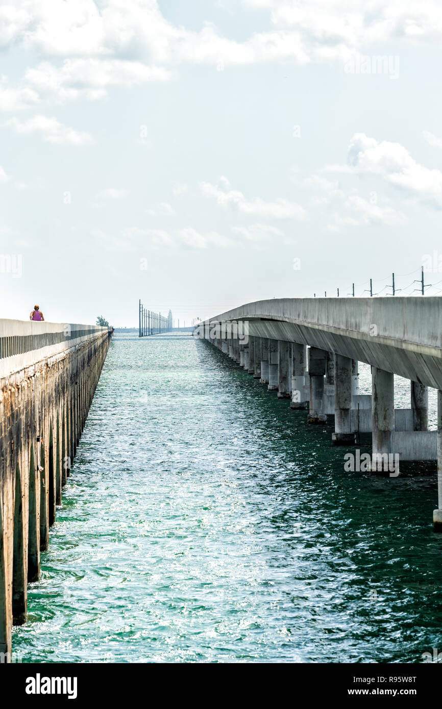 People, woman running at Old Seven Mile Knights Key-Pigeon Key-Moser Channel-Pacet Channel Bridge, overseas highway road, ocean, sea, water at Pigeon  - Stock Image
