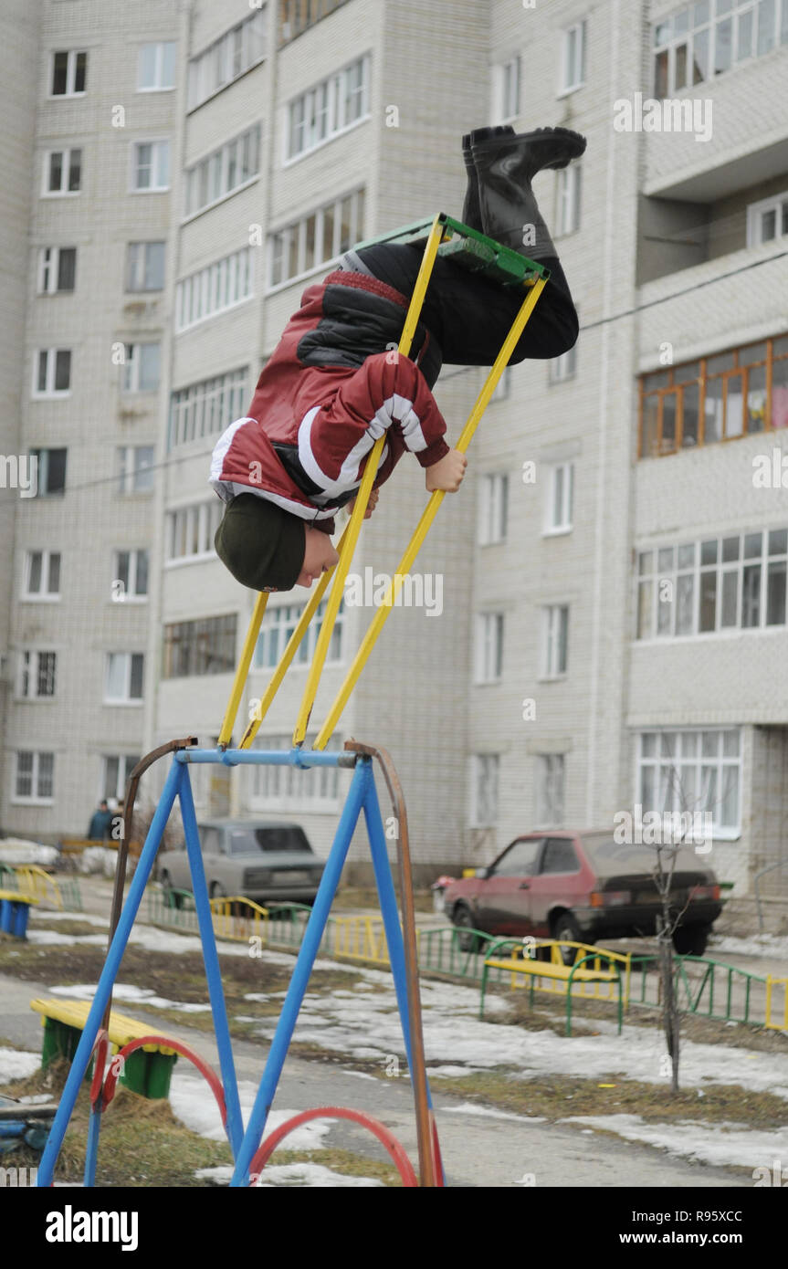 Kovrov, Russia. 7 April 2013. Teen rotates on a swing (performs exercise solnyshko (sun)) in the courtyard of a multi-storey residential building - Stock Image