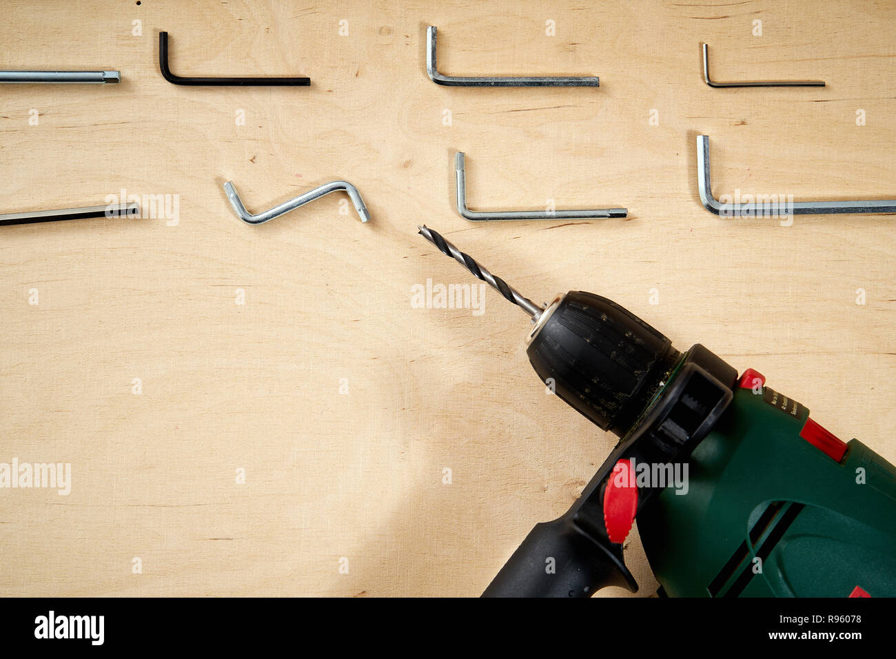 pattern background of various allen keys with drill on wooden work table - Stock Image