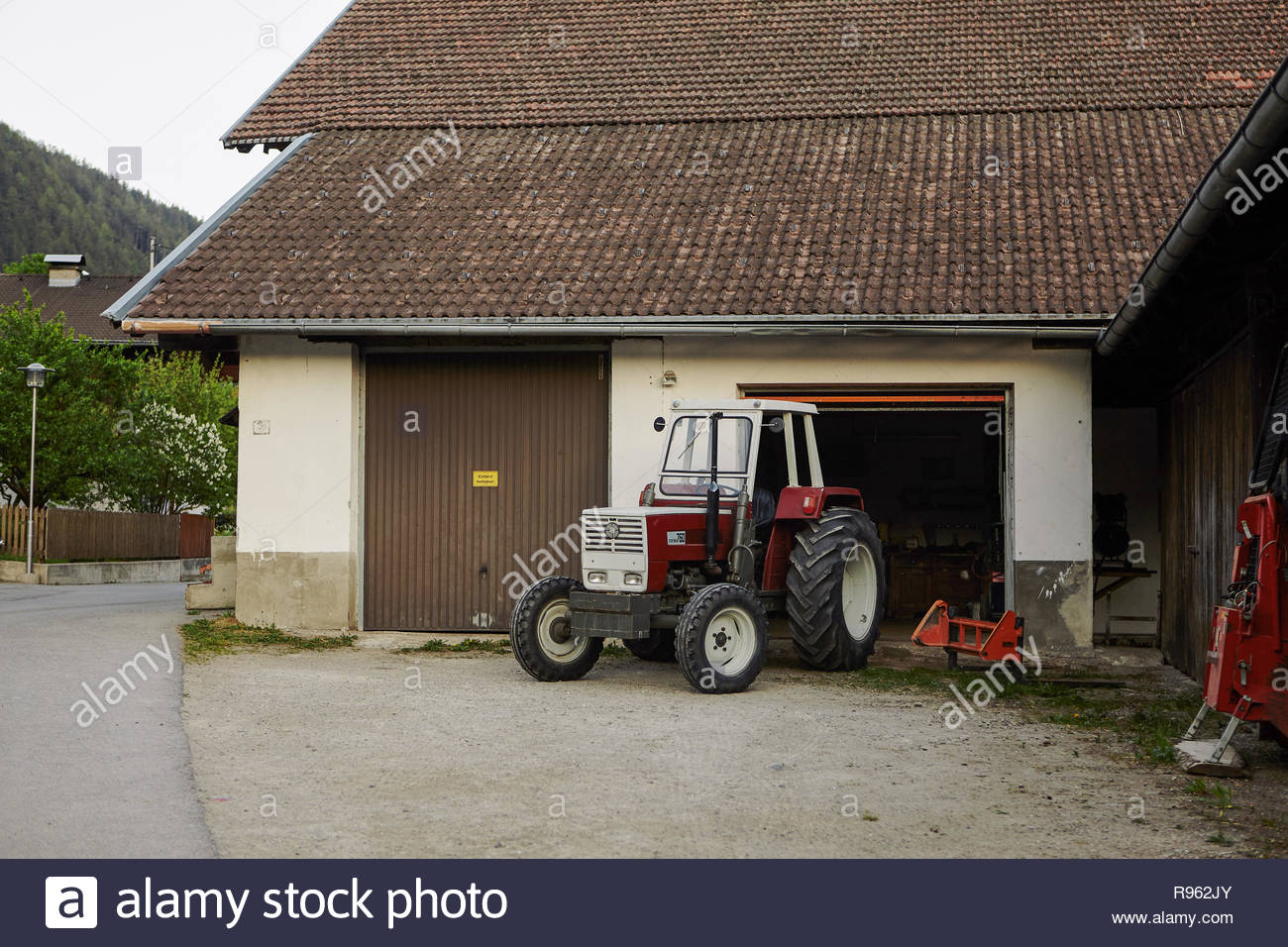 Ainet, Tyrol, Austria May 10, 2011: Barn and red tractor - Stock Image