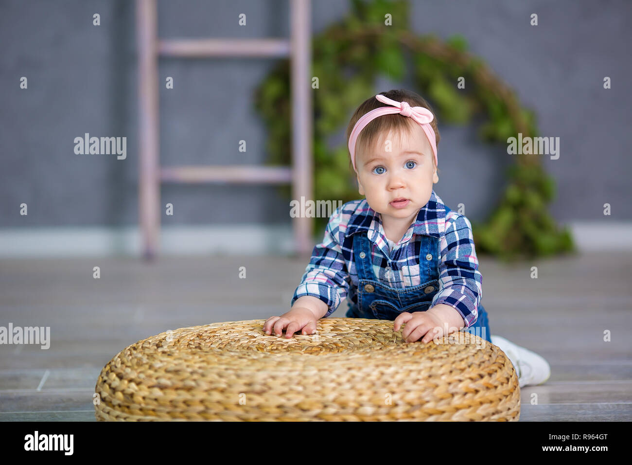 28809af80 Portrait of a cute baby girl on a light background with a wreath of ...
