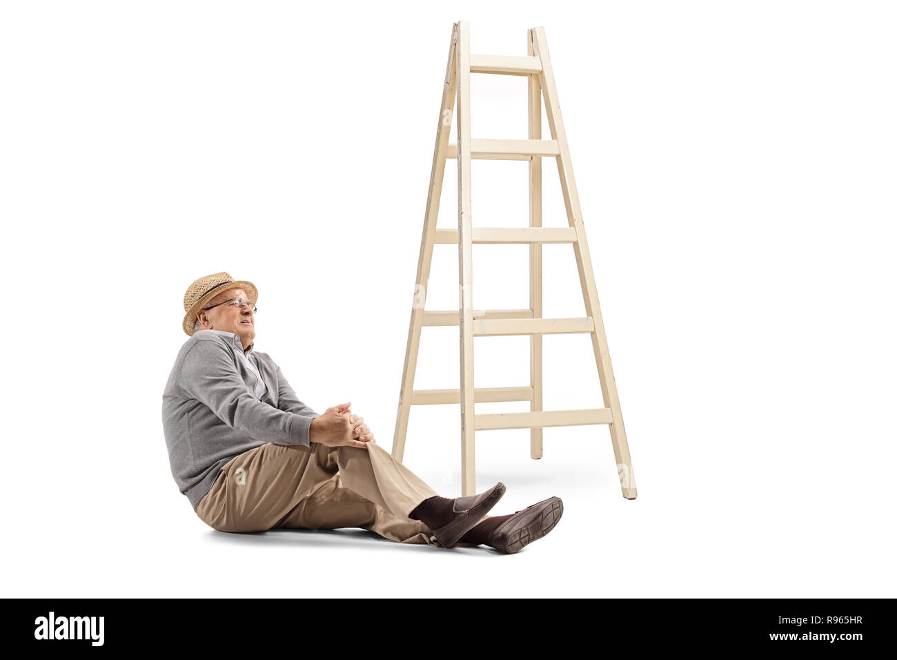 Elderly man fallen off a ladder sitting on the floor and holding his knee isolated on white background - Stock Image