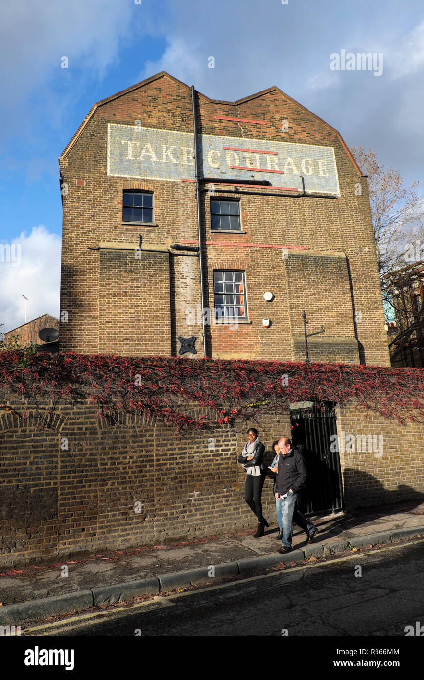 Take Courage Brewery vintage advert sign on the side of brick building in the Borough of Southwark in South London England UK  KATHY DEWITT - Stock Image
