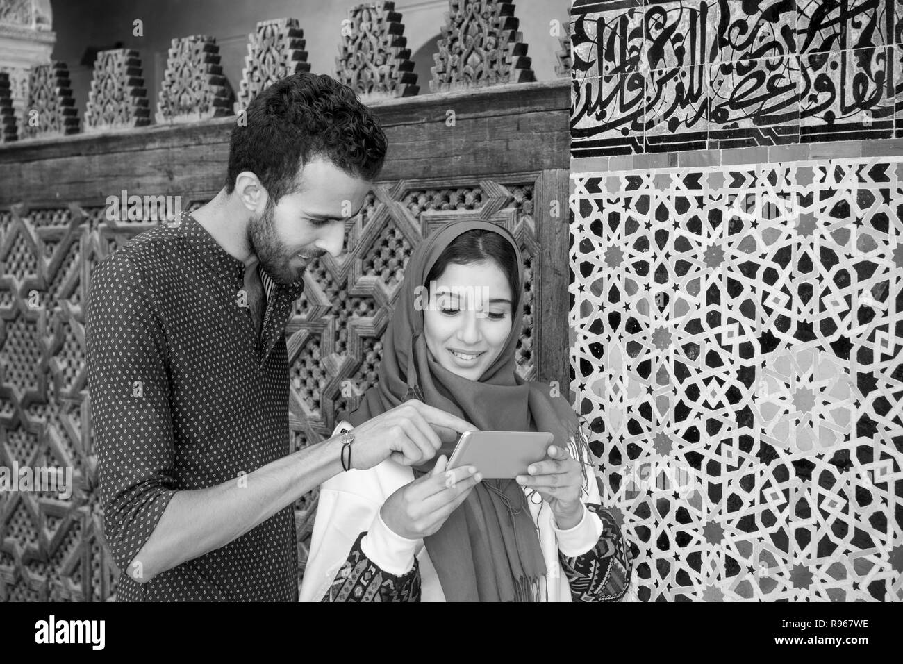 Black and white image of smiling muslim couple looking at cellphone beside the arabesque decorated moroccan wall - Stock Image