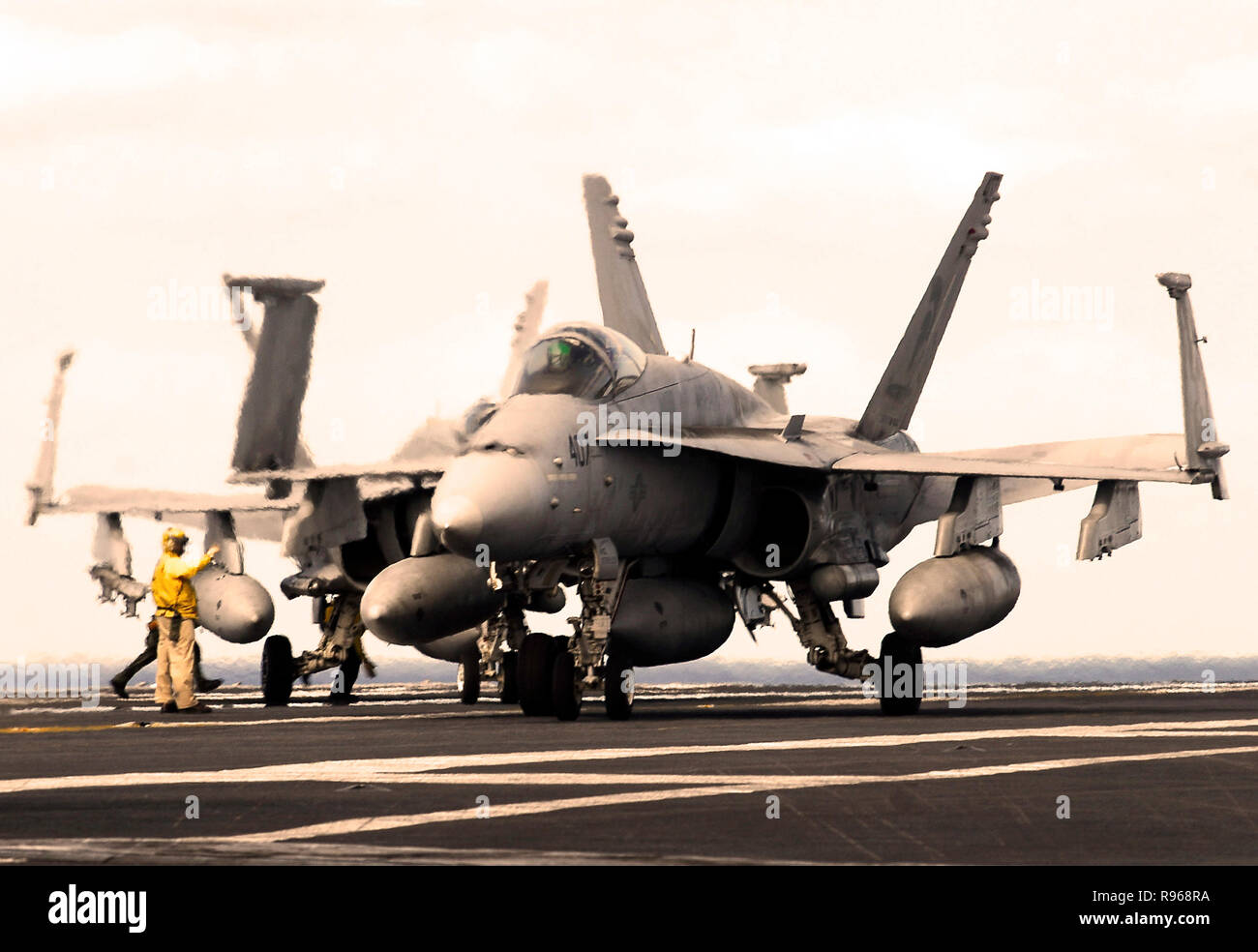A flight deck director guides an F/A-18C Hornet attached to the Argonauts of Strike Fighter Squadron One Four Seven (VFA- 147) onto the flight deck of the Nimitz-class aircraft carrier USS John C. Stennis (CVN 74).  U.S. Navy photo by Mass Communication Specialist 3rd class Jon Hyde Stock Photo
