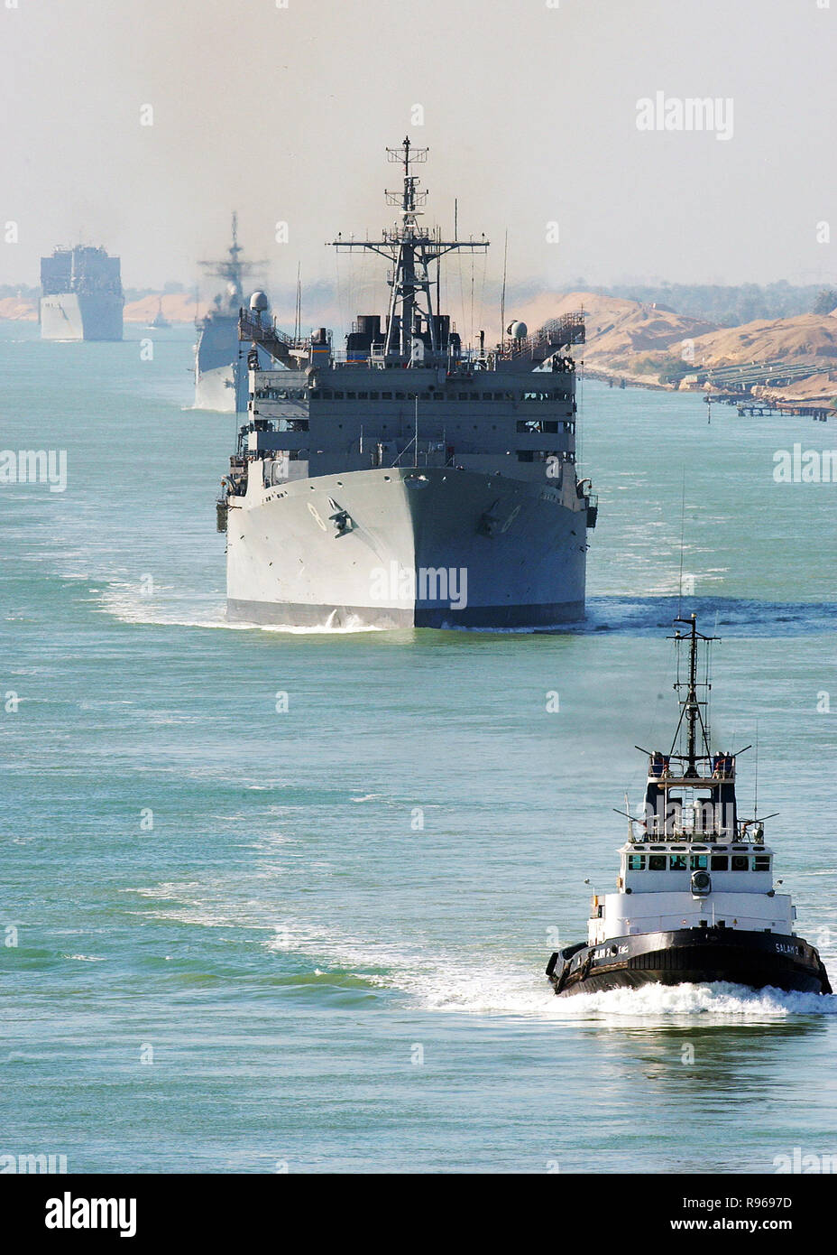 An Egyptian tugboat leads the fast combat support ship USNS Arctic (T-AOE 8), the guided missile cruiser USS Monterey (CG 61), and the combat stores ship USNS Spica (T-AFS 9) northward through the Suez Canal.  DoD photo by Airman Kristopher Wilson, U.S. Navy - Stock Image